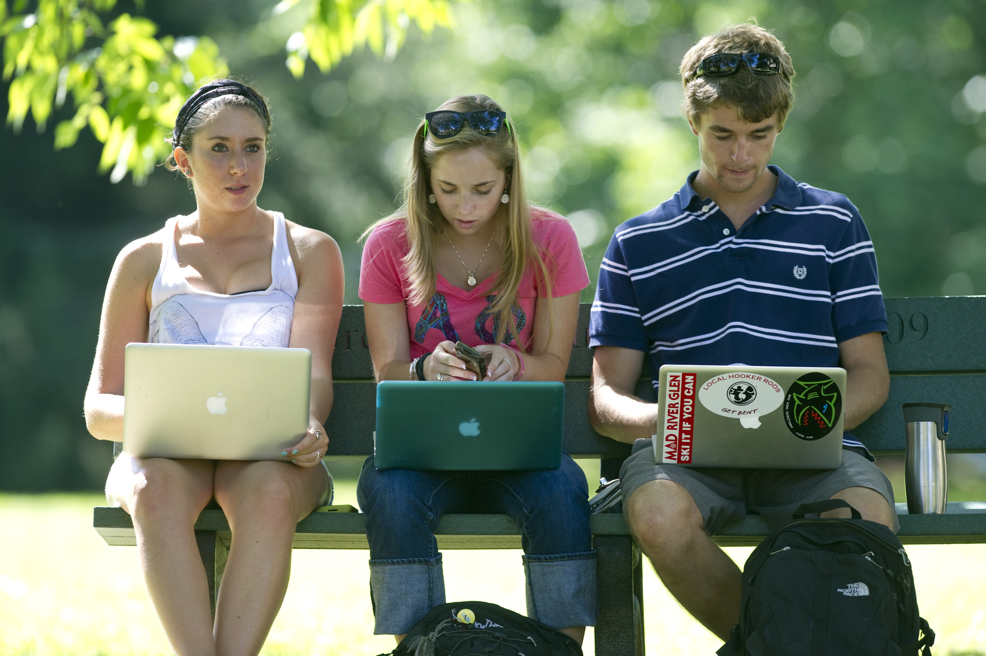 3 students on laptops outside
