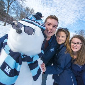 3 students with snowman in UMaine hat and scarf