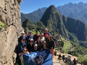 students in mountains of Peru with UMaine banner