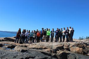 Students on the rocks in front of the ocean in Acadia National Park