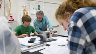 teacher helping student in science classroom