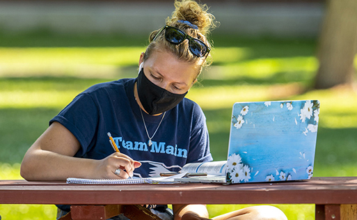 student studying outside with mask on